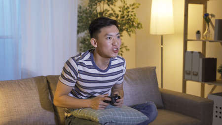 profile of male player having obsession with video games playing with handheld control in excitement.