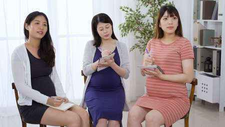 chinese pregnant ladies sitting together staring ahead and taking notes. asian female paying attention to what the teacher says in antenatal class. 版權商用圖片