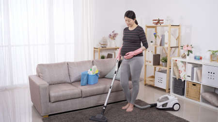 elegant asian pregnant woman holding belly while vacuuming carpet at home. background cozy bright living room with sofa. authentic lifestyle 版權商用圖片