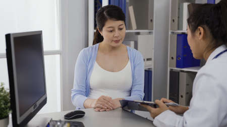 asian female in her last trimester listening to her doctor's explanation in hospital. cropped view gynecologist showing the test result to her patient at desk, holding clipboard. authentic lifestyle