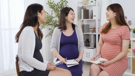 group of taiwanese happy mothers-to-be meeting up in antenatal class. lady in orange striped dress nodding to show understanding after hearing the sharing.