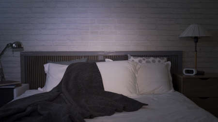 interior of empty bedroom at night, with unmade bed and tv left on. modern living space with white bedding and grey blanket
