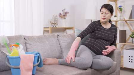 full length asian woman in her last trimester disturbed with lower limb edema after cleaning house all day. pregnant mom messaging legs to ease pain on sofa at home. genuine lifestyle