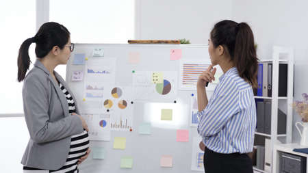 scheme meeting at office. asian employee touching chin, discussing with her pregnant boss in front of whiteboard with sticky notes and charts during briefing. teamwork, authentic lifestyle