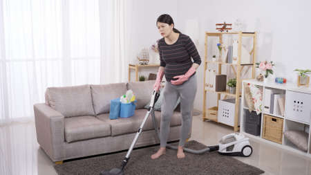 full length asian female in her third trimester feeling sudden painful contraction while cleaning floor  at home. stroking belly with discomfort facial expression. genuine lifestyle