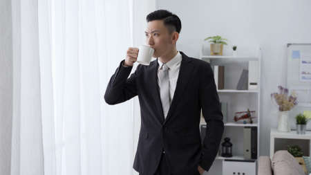 male ceo is sipping morning coffee by window with serious expression. asian man in black suit with hand in pocket is looking outside in contemplation