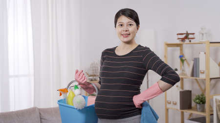portrait asian pregnant woman smiling face at camera in rubber gloves, carrying a bucket of detergent and cleaning equipments. background bright home interior. profile and style concept