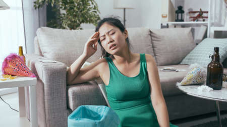 korean lady sitting by sofa suffering from hangover after party. Stockfoto