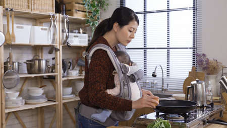 asian female parent carefully holding young child with carrier is preparing breakfast and cracks egg into pan in kitchen in early morning Reklamní fotografie