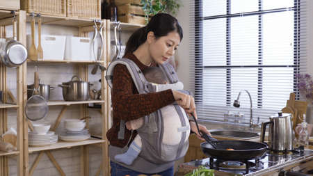 traditional eastern chinese wife carrying baby and cutting vegetable while waiting for food to heat up in pan in home kitchen.