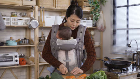 charming asian japanese female parent cutting carrots and calming with verbal soothing her cute baby girl in morning kitchen.