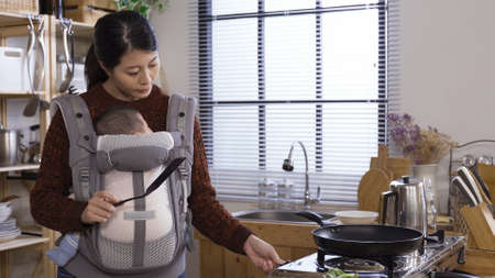 elegant asian chinese female manager carrying baby girl while making breakfast meal at modern home kitchen.