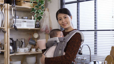 taiwanese lady looking at camera while petting her lovely daughter and having cup of tea in the morning in modern house. Reklamní fotografie