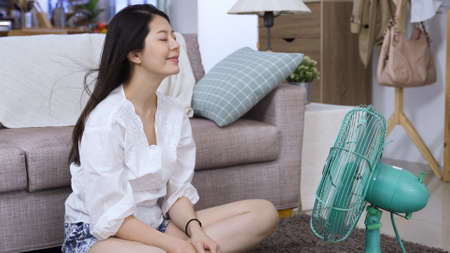 smiling young asian female breathing a sigh of relief and daydreaming while having great time with cool breeze at home living room.