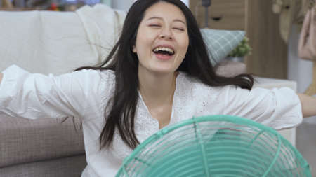 closeup cheerful asian chinese lady behind fan feeling comfortable is picturing herself blown by sea breeze and let out a cry with satisfaction