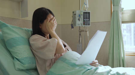 depression and sadness asian pregnant woman reading diagnosis paper and crying while resting in bed in hospital room