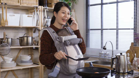 calm and unhurried asian korean career woman holding toddler and talking on cellphone while cooking in the modern kitchen in the morning. Reklamní fotografie