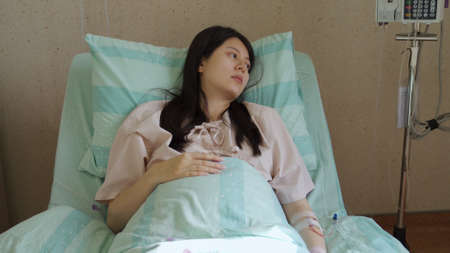 camera movement korean female with lingering illness is looking away in depression while lying in bed in hospital room. Reklamní fotografie