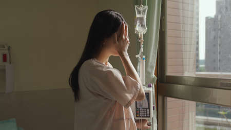 crying woman standing with drip stand in front of window is thinking about her illness and wiping away tears with hands. Reklamní fotografie