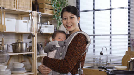 beautiful asian millennial woman holding baby in arms is experiencing pure joy as a new mother while standing in home kitchen Reklamní fotografie