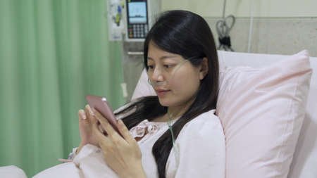 portrait of girl with feeble look but recovering well from coronavirus disease is phubbing in bed in ward