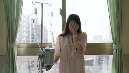 portrait of hospitalized female cancer patient back on window holding iv drip stand and weeping in despair.