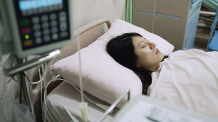 high angle view illness asian woman cancer patient is sleeping  and recovering alone in ward after operation in hospital.