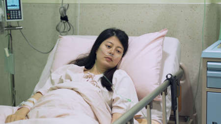 view form medical partition taiwanese female in vegetative state resting alone on bed in bright hospital.