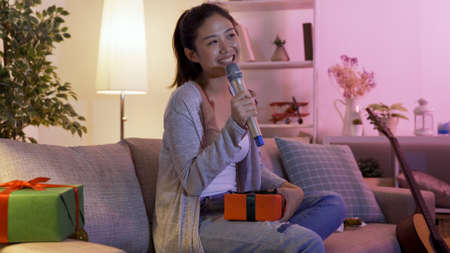 portrait of Chinese girl seated on couch with gift is having one-man Christmas karaoke party at home in dark night.