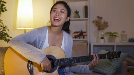 waist up happy beautiful asian girl entertaining herself by practicing guitar and singing songs in the living room. Reklamní fotografie