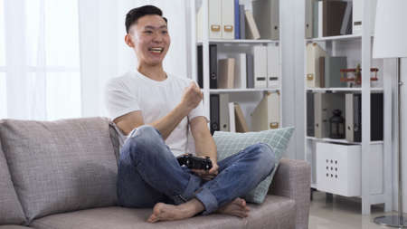 handsome young asian japanese man holding wireless controller is playing video game in concentration on sofa at home.