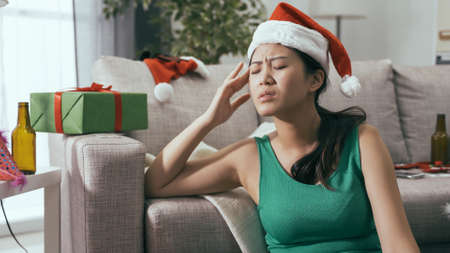portrait unhappy asian japanese girl in green dress and santa hat is massaging her head to ease the discomfort from hangover after christmas party.