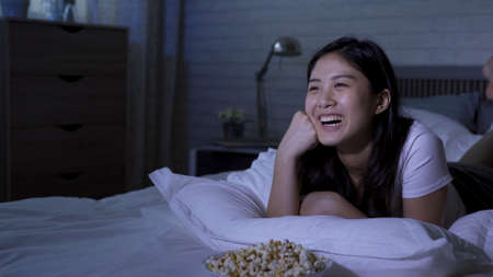 cheerful laughing asian taiwanese lady lying prone on bed is enjoying popcorns and seeing comedy during lockdown at night