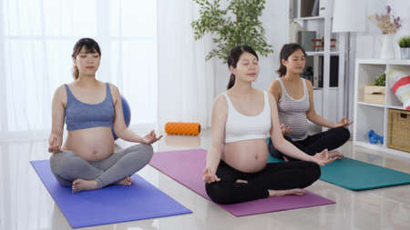 asian pregnant yoga instructor in white sportswear bra and bare belly is leading a group class for mother-to-be to practice meditation in her studio