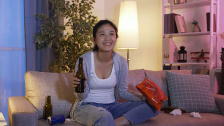 asian happy young college girl gulping beverage from bottle and eating snacks while binge-watching episodes on tv in messy living room at night.