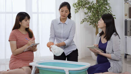 patience asian midwife explaining the steps and teaching two young moms how to bathe a newborn baby.