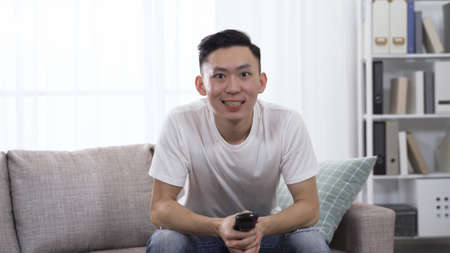 handsome asian male sitting on sofa holding remote control is watching ball game with full attention. Reklamní fotografie
