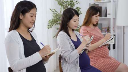 happy asian japanese ladies learning knowledge about how to take care of themselves during pregnancy and writing down notes on notebook.
