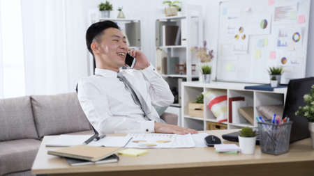 joyful laughing asian chinese businessman having mobile phone conversation in relaxed mood in home studio.