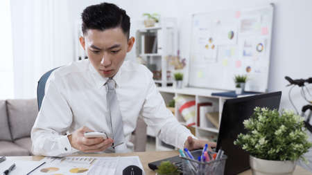 serious asian man in shirt and tie is checking information on smart phone and entering data on notebook while sitting at work desk.