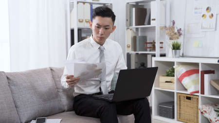 asian korean male employee is reading financial analysis on paper and typing up data on laptop computer while sitting on sofa in living room.