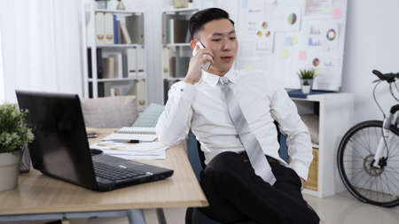 confident asian man having cellphone conversation with coworkers and discussing about new teamwork project in bright office