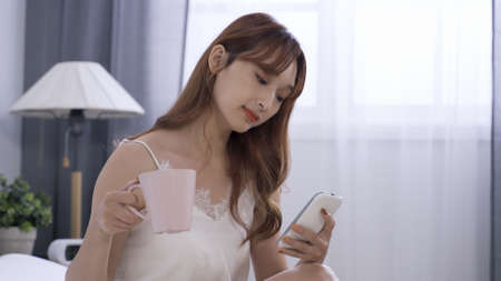 camera movement woman wearing white lace tank top is checking online messages on phone and drinking cup of coffee while sitting in bedroom at home.
