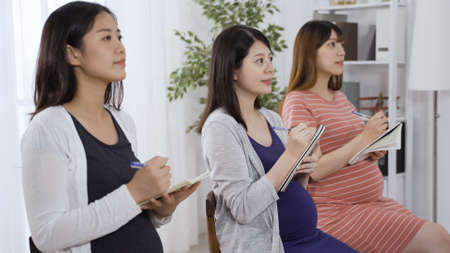 three happy japanese pregnant ladies learning new knowledge and listening attentively in class before newborn babies come out Reklamní fotografie