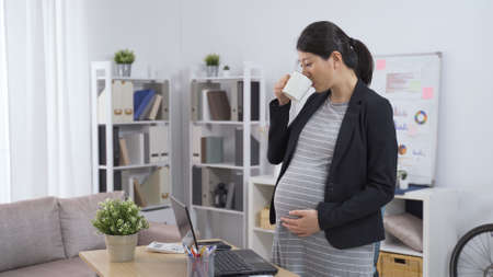 elegant asian chinese pregnant ceo woman standing in the office is drinking tea and touching her tummy while reviewing project on laptop
