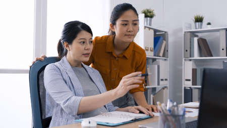 group of asian female workers looking at laptop together and having discussion in bright modern office.