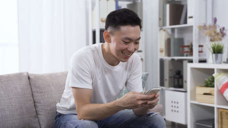 portrait cheerful smiling asian chinese guy seated on comfortable couch is typing message with smartphone.