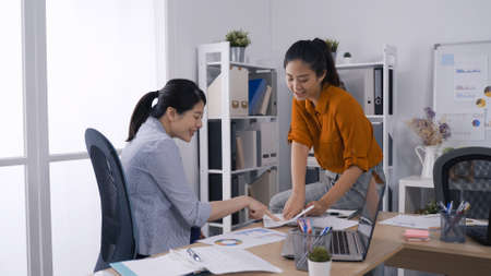 two cheerful asian female business entrepreneurs looking discussing at report in modern office in the morning. Reklamní fotografie