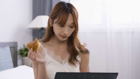 front view beautiful asian korean lady having bun while reading online news on laptop computer in leisure time at home.