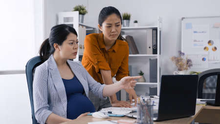 unhappy expectant woman ceo looking and pointing at computer screen with sales performance of the season while meeting with female colleague. Reklamní fotografie